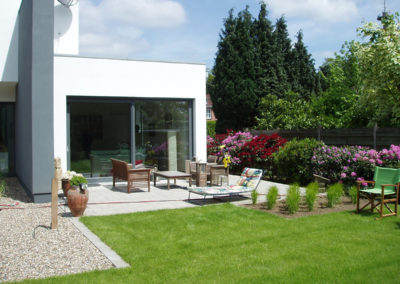 Terrassenpflasterung aus Beton-Großformatpflaster mit geraden Beetelementen, bepflanzt mit Gräsern sowie angelegte Kiesbeete