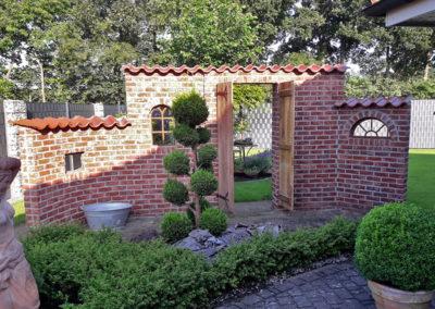 Ziermauer im historischen Stil mit alten Fenstern aus Gusseisen und rustikaler Eichentür