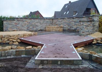 Gartenteichanlage mit Sichtschutzmauer aus Schiefer in Riemchenoptik, Trockenmauer-Hochbeete und beleuchteter Terrasse in Holzoptik als Steg über den Teich