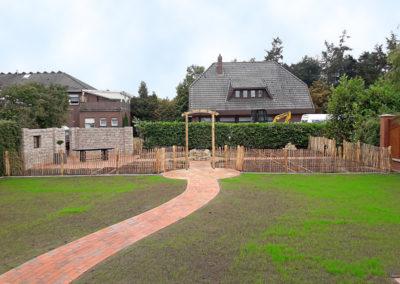 Bauerngarten mit vielen Einzelbeeten, eingefasst mit einem Staketenzaun sowie Terrasse mit Sichtschutz aus Betontrockenmauersteinen