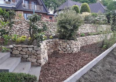Hangbegrenzung mit Trockenmauer aus Bruchsteinen und Treppenanlage aus Betonblockstufen