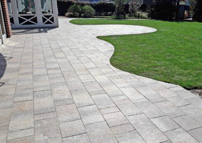 Geschwungene Gartenweg- und Terrassenpflasterung aus beschichteten Betonsteinplatten