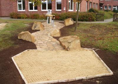 Pumpenanlage mit geschwungenem Wasserlauf aus Sandstein-Polygonalplatten und Sandbeet zum Matschburgen bauen