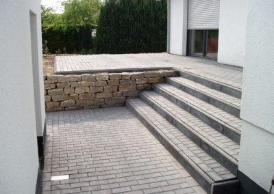 Terrassen- und Stufenpflasterung aus schlichtem Betonstein, Trockenmauer als Beeteinfassung aus Muschelkalk