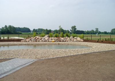 Einfassung des Teichs mit Rheinkies und Teilabgrenzung durch Findlinge