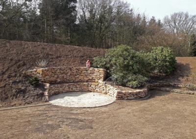 Trockenmauer mit Abstufung aus Ibbenbürener Sandstein sowie Pflasterkreis aus gerumpelten Betonsteinen