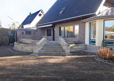 Hoch aufgebaute, geschwungene Terrasse mit Hochbeeten und Blockstufen aus geschliffenem Sandstein